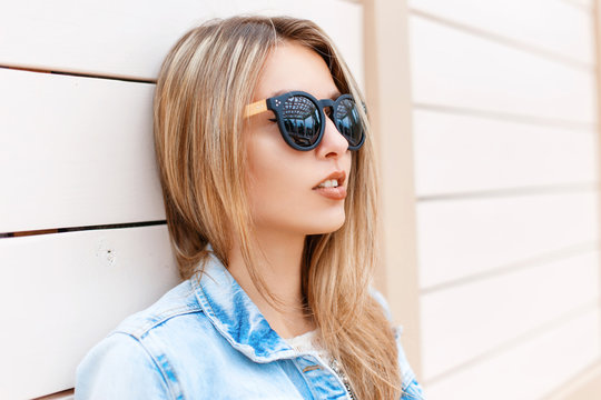Close-up portrait of a beautiful young girl in sunglasses and denim jacket on the beach near the wooden wall