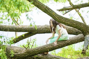Little Girl in white dress sitting on tree trunk over green gras