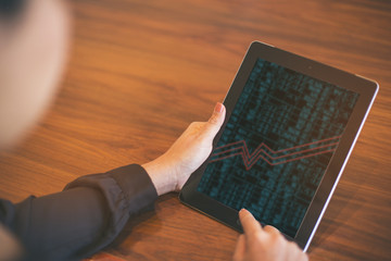 Businesswoman checking the stock market on digital tablet in off