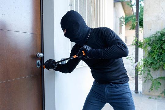 Burglar trying to force a door lock using a crowbar