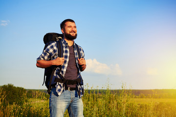 Smiling man with rucksack standing in the field and enjoying the