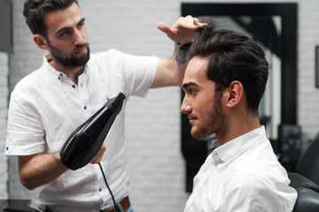 professional hairstylist is drying the client's hair with hairdryer