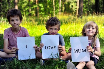 Three kids with a sign I love mum