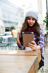 Young woman using digital tablet while sitting in coffee shop