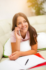 Little girl lying in bed using smartphone at home