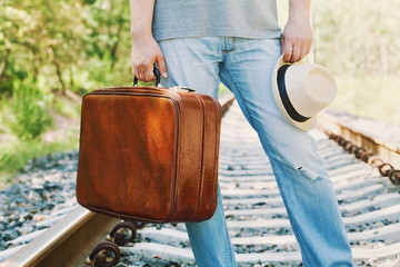 Man with vintage suitcase and hat standing on the railway on a sunny day. Holidays, vacation, travel and trip. Passenger with luggage outdoors.
