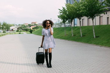 Full body portrait of traveling woman walking with suitcase and mobile phone
