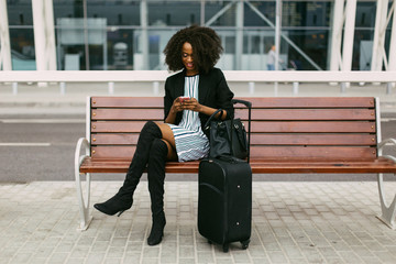 Full length of businesswoman texting with cell phone while sitting by luggage on bench against building