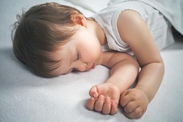 Newborn baby sweet sleeping on a white bed