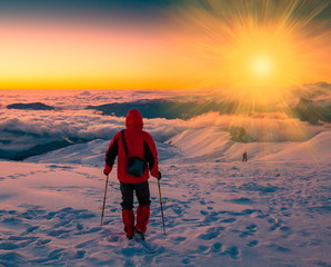A man in mountain sunset winter. Unique. Sunny rays. Christmas