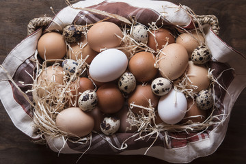 Different kind of raw eggs in a basket