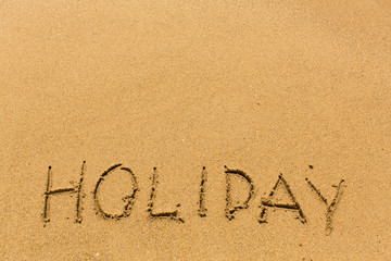 Holiday - inscription by hand on the beach sand.