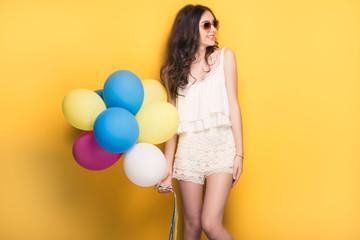 Teenage girl with colorful balloons, studio shot.