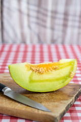 Sliced melon on the kitchen wooden board and kitchen knife