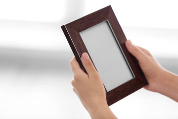 Female hands holding photo frame on light background