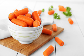 Small baby carrots in soup plates on cutting board