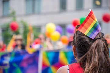 A female spectator with a rainbow flag hair stick is watching th