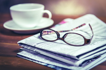 Glasses on pile of newspaper with coffee cup in background.Vintage tone photo with selective focus on glasses.