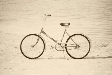 Ancient bicycle on beach - retro sepia