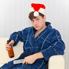 Man in Christmas cap with remote control and beer