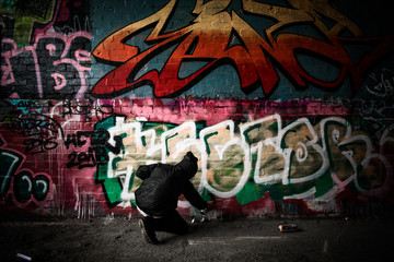 Hooded boy finishing graffiti