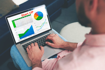 Experienced businessman looking at financial data with graphics and charts