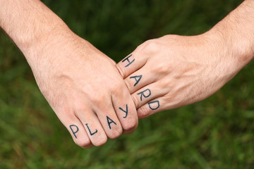 Man fist with fake tattoo on green grass background