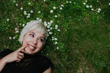 Beautiful blonde girl smiling while lying on grass with  flowers