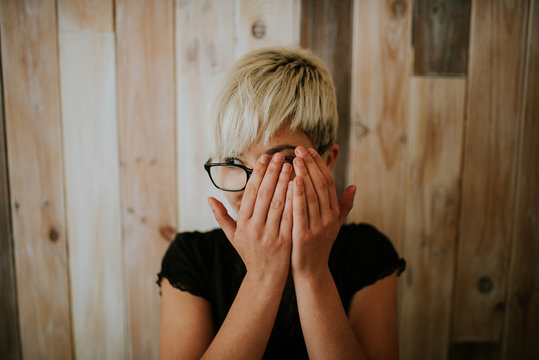 Young girl in glasses covering face with hands