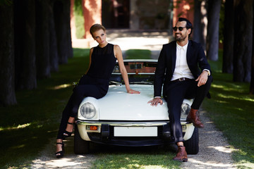 Romantic and fashionable couple posing on luxury cabriolet car