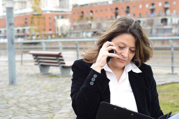 Portrait of business woman talking on her smartphone and reading