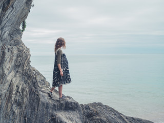 Young woman standing on rocks and looking at sea