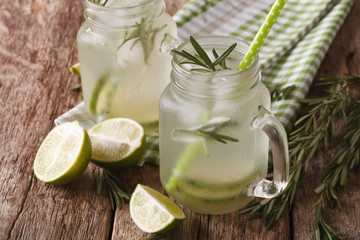 Summer cold drink with lime, ice and rosemary macro in a glass jar. Horizontal