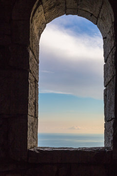 View at blue sky from ancient arch window in stone wall