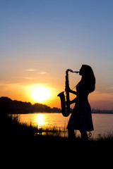 silhouette of a young woman playing a wind instrument at dawn on the river