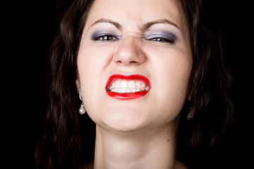 Close-up woman looks straight into the camera on a black background. expresses different emotions, showing teeth, showing grin growls
