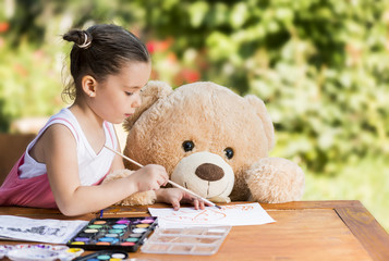 Adorable little girl painting outdoor in a sunny summer day with her teddy bear friend. Outdoor education concept