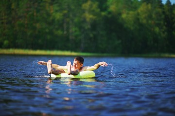 relaxed young man lying on inflatable ring in lake and admiring the stunning views. Away on a blurred background forest and sky.