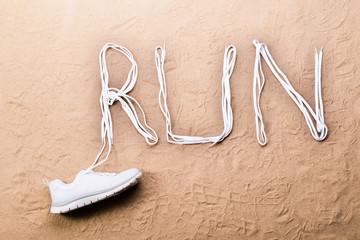 Running shoe and run sign made of shoelaces, sand
