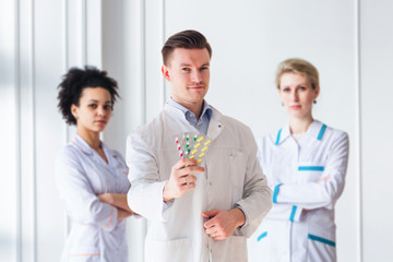 Attractive male doctor with pack of pills in front of his medical team