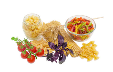 Several different uncooked pasta, wheat spikes, basil, cherry to