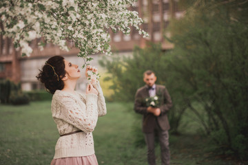 Happy couple in the blooming garden. Man dressed in suit. Woman in the dress and sweater