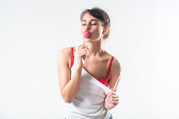 Young brunette model with lollipop posing studio shot on white background, not isolated