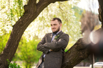 bearded man dressed in grey suit stands near the tree in the park