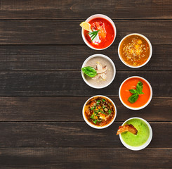 Six soups at brown wood, top view with copy space