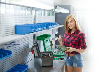 Young brunette woman in checked shirt and jeans in a garage work with electronic plate. Auto diagnostic service