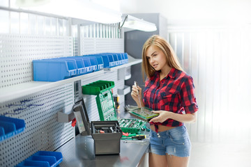 a young woman in a garage work with electronic plate. Auto diagnostic service