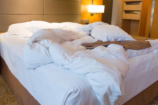 Unmade bed in hotel bedroom
