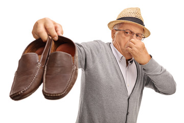 Disgusted senior holding stinky shoes