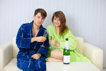 Husband and wife in a holiday on sofa with champagne wine